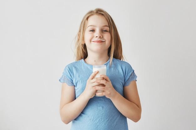 Menina bonita com cabelo loiro na camiseta azul com leite cai no rosto, feliz em começar o dia com um copo grande de bebida saudável.