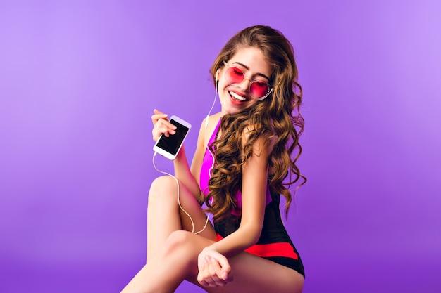 Menina bonita com cabelo longo cacheado em óculos de sol rosa sobre fundo roxo no estúdio. ela usa maiô e escuta música com fones de ouvido.