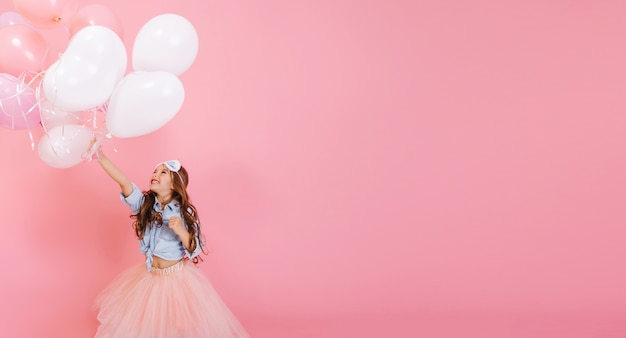 Menina bonita, com cabelo longo cacheado, em saia de tule rosa se divertindo com voar acima de balões isolados no fundo rosa. infância feliz de criança incrível expressando positividade. lugar para texto