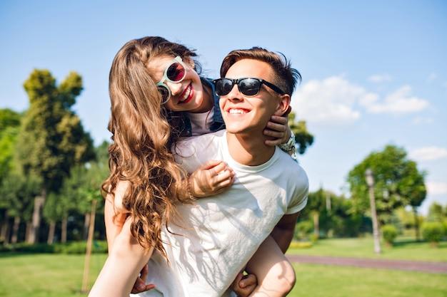 Menina bonita com cabelo longo cacheado está montando nas costas do cara bonito no parque. eles usam óculos escuros e se divertem.