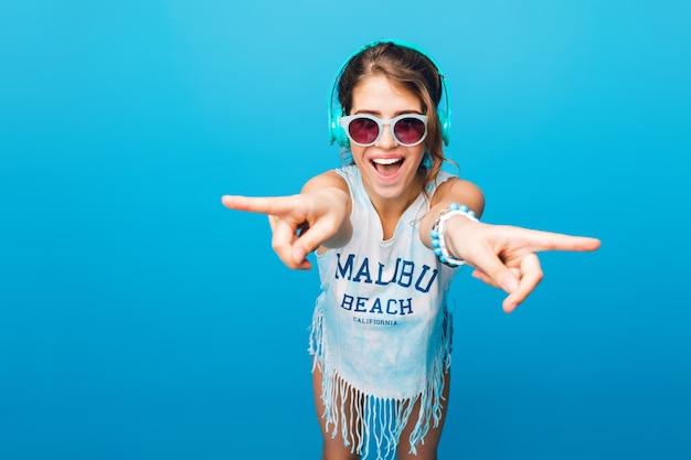 Menina bonita com cabelo longo cacheado na cauda em óculos de sol azuis se diverte sobre um fundo azul no estúdio. ela veste camiseta branca, bermuda e escuta música com fones de ouvido azuis.