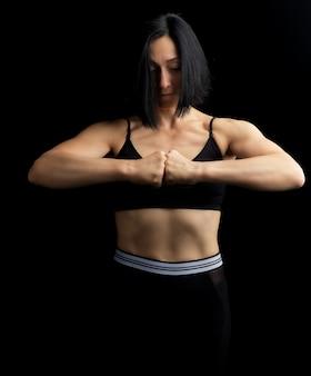 Menina bonita com cabelo preto, aparência atlética, punhos na frente do peito