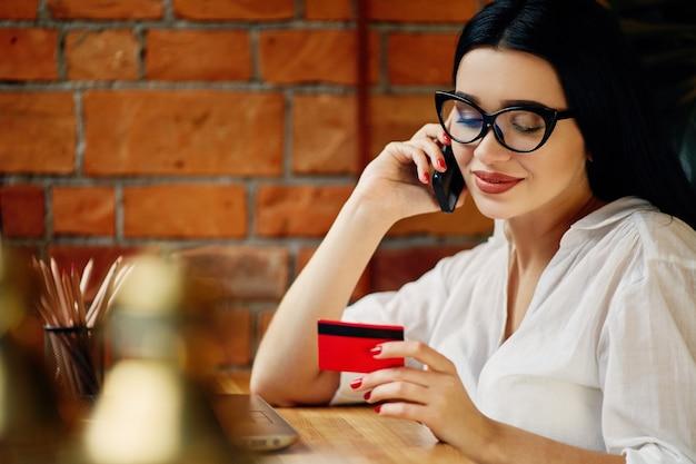 Menina bonita com cabelo preto, usando óculos, sentado no café com laptop, telefone celular, cartão de crédito e xícara de café, conceito freelance, compras online, camisa branca.
