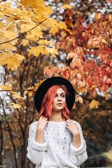 Menina bonita com cabelo vermelho e chapéu andando no parque, outono.
