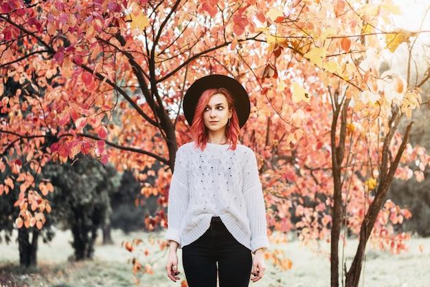 Menina bonita com cabelo vermelho e chapéu que anda no parque, tempo do outono.