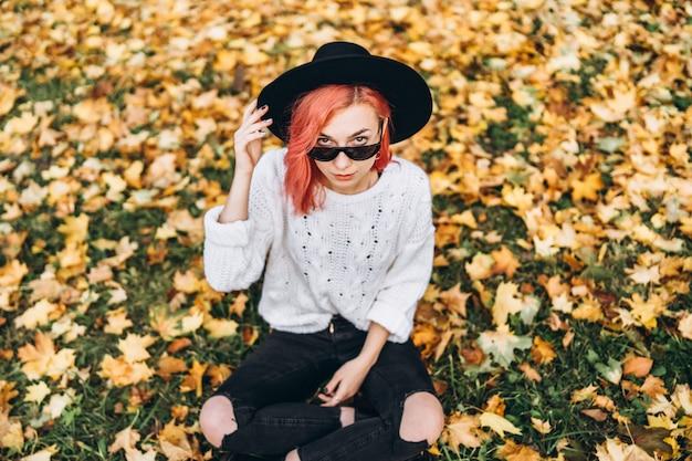 Menina bonita com cabelo vermelho e chapéu relaxante no parque, outono.
