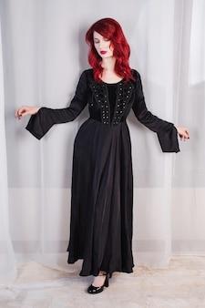 Menina bonita com cabelo vermelho e maquiagem natural e pele pálida. uma mulher em um vestido preto retrô. modelo posando no estúdio. a aparência incomum. mulher insidiosa bruxa malvada.