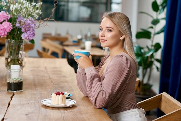 Menina bonita com cabelos loiros e olhos azuis, tomando café no café.