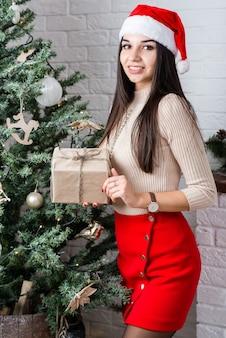 Menina bonita com caixa de presente no quarto decorado com natal.