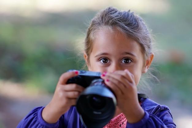 Menina bonita com câmera fotográfica tira fotos