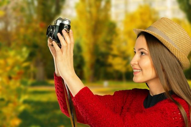 Menina bonita com câmera no parque de outono