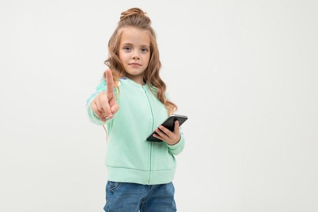 Menina bonita com capuz azul fica com smartphone isolado no fundo branco