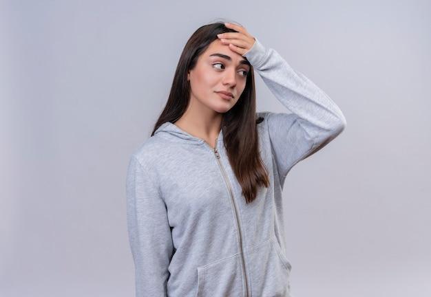 Menina bonita com capuz cinza olhando para longe tocando a cabeça por engano, parecendo confuso conceito de memória ruim em pé sobre um fundo branco