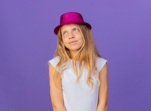Menina bonita com chapéu de férias olhando para o lado com um sorriso no rosto, conceito de festa de aniversário em pé sobre fundo roxo