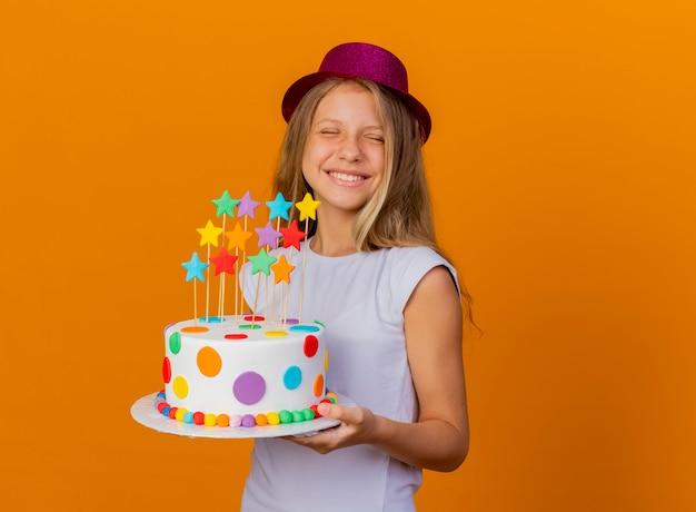 Menina bonita com chapéu de férias segurando bolo de aniversário animada e animada, conceito de festa de aniversário em pé sobre fundo laranja