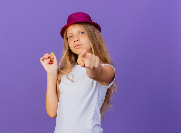 Menina bonita com chapéu de festa apontando com o dedo indicador para a câmera com uma cara séria, conceito de festa de aniversário em pé sobre fundo roxo