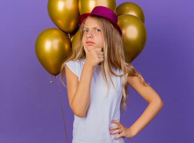 Menina bonita com chapéu de natal com um monte de balões e expressão pensativa