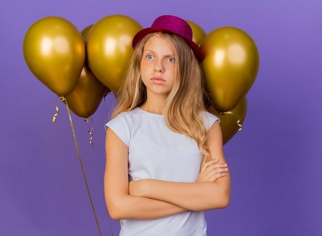 Menina bonita com chapéu de natal com um monte de balões olhando para o lado intrigada