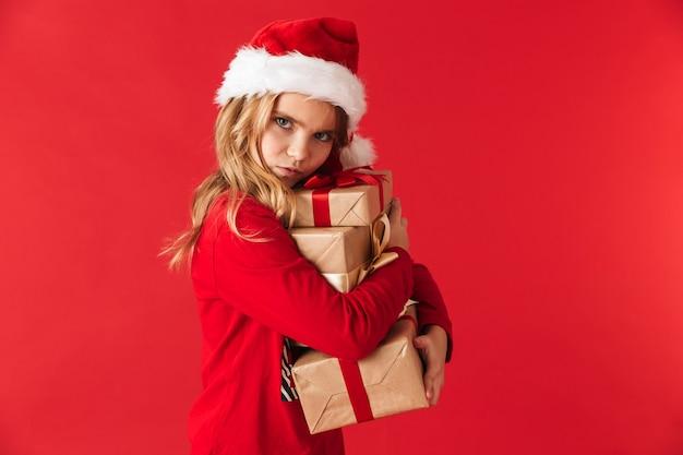 Menina bonita com chapéu de natal isolada, segurando uma pilha de caixas de presentes