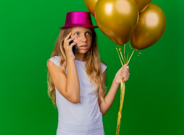 Menina bonita com chapéu de natal segurando um smartphone