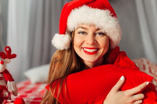 Menina bonita com chapéu de natal sorrindo para a câmera enquanto segura o travesseiro vermelho