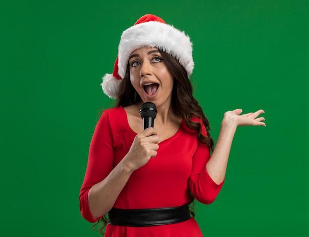 Menina bonita com chapéu de papai noel segurando um microfone e mostrando a mão vazia olhando para cima cantando isolado sobre fundo verde