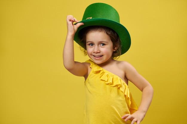 Menina bonita com chapéu irlandês de duende verde sorrindo para a câmera em uma superfície amarela