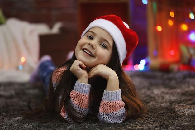 Menina bonita com chapéu vermelho deitada em uma sala decorada de natal