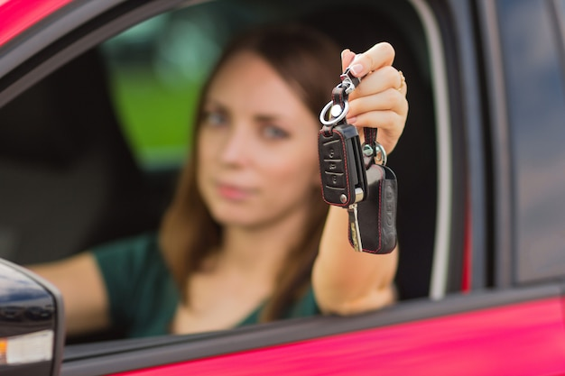 Menina bonita com chaves do carro na mão, conceito de comprar um carro novo