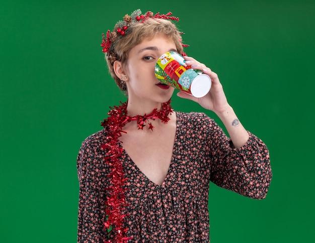 Menina bonita com coroa de flores de natal e guirlanda de ouropel em volta do pescoço, bebendo café em um copo de plástico de natal isolado na parede verde com espaço de cópia
