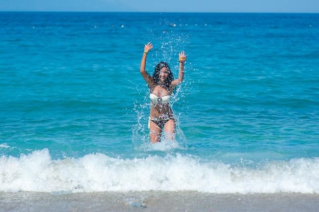 Menina bonita com corpo perfeito em traje de banho biquíni brincando com água na praia das maldivas