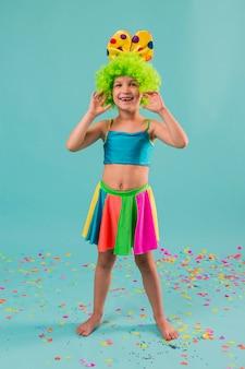 Menina bonita com fantasia de palhaço e confetes
