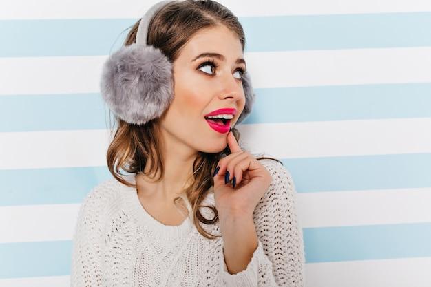 Menina bonita com fones de ouvido desvia o olhar com interesse Foto gratuita
