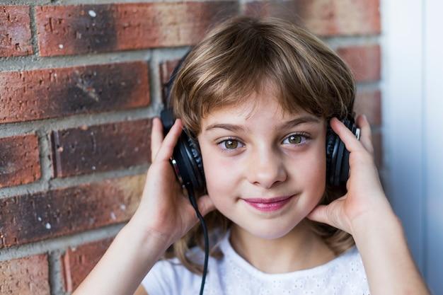 Menina bonita com fones de ouvido em casa ouvindo música e sorrindo, conceito de tecnologia e música