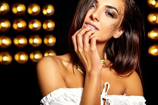 Menina bonita com glitter dourado no rosto