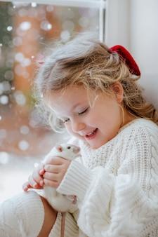 Menina bonita com laço vermelho sentada perto da janela segurando um ratinho branco