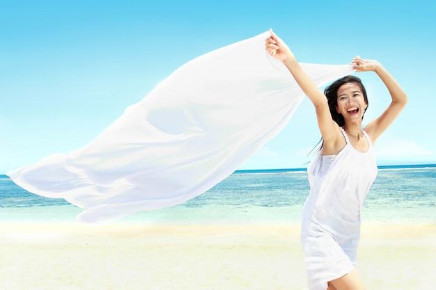 Menina bonita com lenço branco na praia