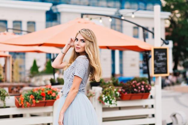 Menina bonita com longos cabelos loiros, sorrindo para a câmera no fundo do terraço.