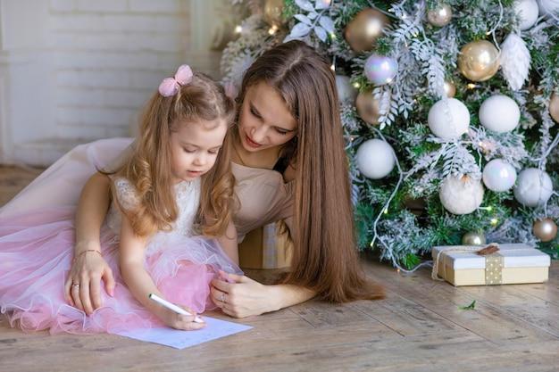 Menina bonita com mãe escrevendo carta para o papai noel no ano novo. criança adivinhando para o natal debaixo da árvore de natal.