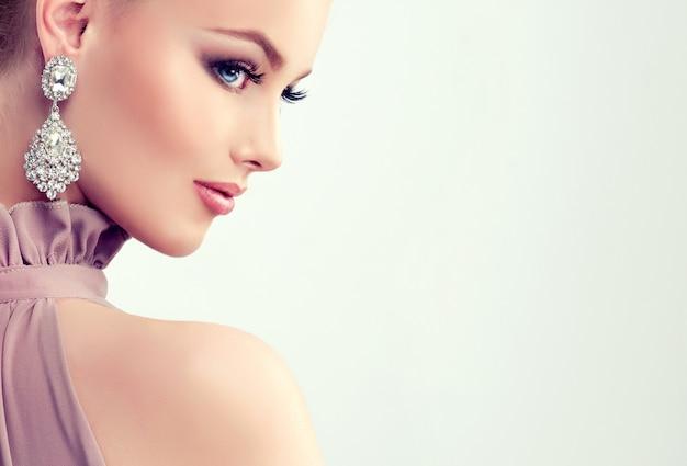 Menina bonita com maquiagem de noite e grandes brincos de jóias