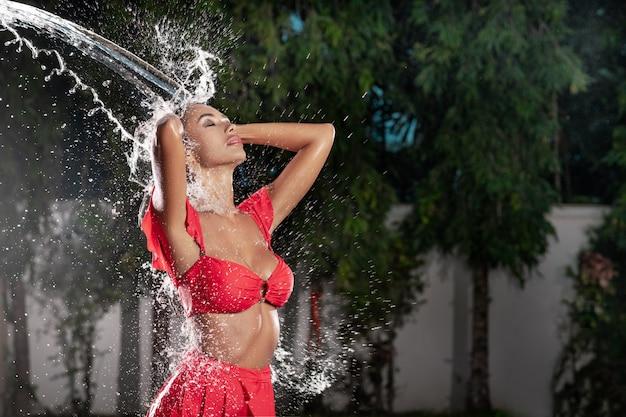 Menina bonita com maquiagem em um maiô vermelho moda sob esguicho de água com a pele fresca