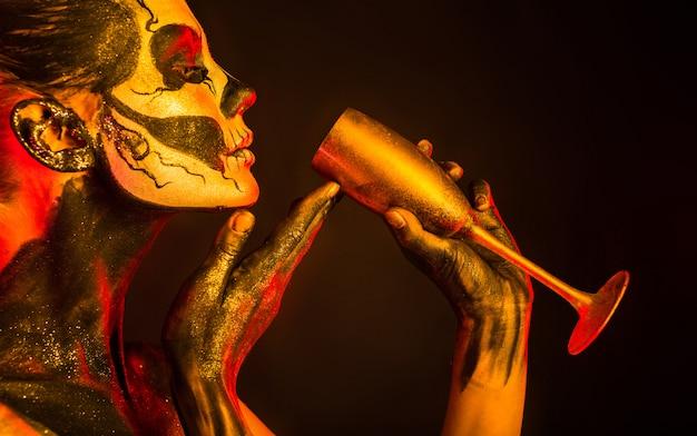 Menina bonita com maquiagem esqueleto detém vidro