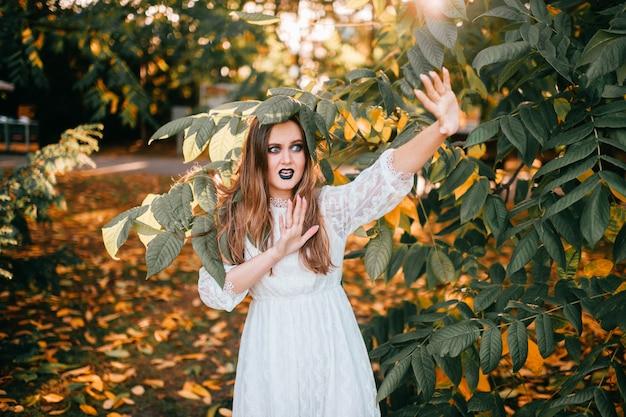 Menina bonita com maquiagem gótica e expressão de rosto engraçado, posando no parque de verão.