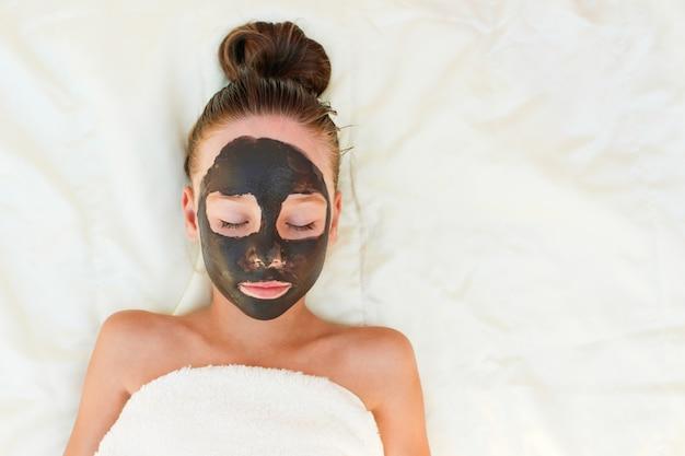 Menina bonita com máscara de argila preta facial.