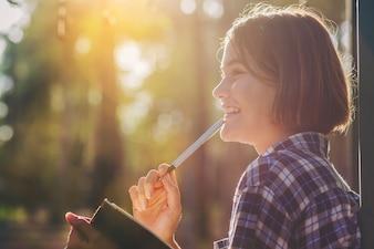 Menina bonita com notebook faz uma pequena nota enquanto educação de viagem ao longo do caminho