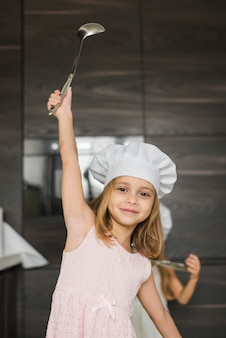 Menina bonita com o braço levantado segurando concha usando chapéu de chef