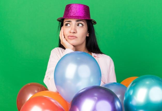 Menina bonita com olhar insatisfeito com chapéu de festa em pé atrás de balões, colocando a mão na bochecha isolada na parede verde