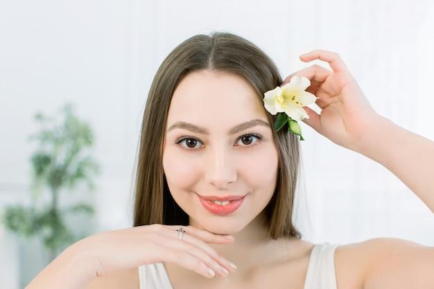 Menina bonita com olhos castanhos e pele fresca que levanta no fundo claro com flor, conceito dos cuidados com a pele, termas da beleza, bio produto. horizontal