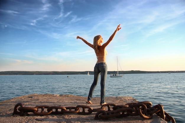 Menina bonita com os braços abertos em pé em um cais