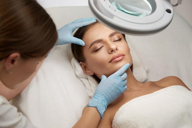 Menina bonita com os olhos fechados deitada em uma clínica de beleza sob a luz e a esteticista verificando seu rosto com luvas